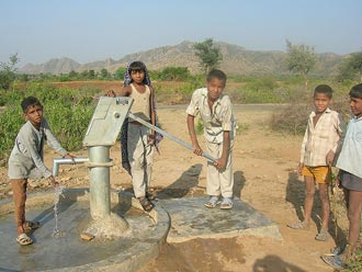 Children pumping water from a tube well